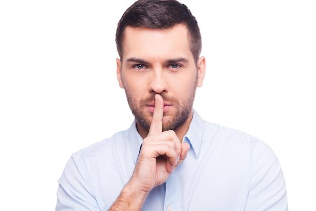 Храни мой секрет! серьезный молодой человек в рубашке, держащий палец на губах и смотрящий в камеру, стоя на белом фоне