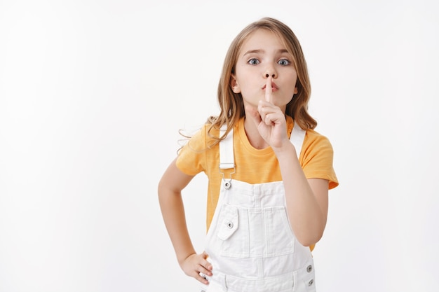 Keep quiet please. determined obedient cute blond girl child showing hush sign, shushing asking silence, hold finger on lips turn off loud music, sharing secret, stand white wall