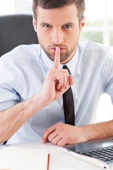 Keep silence! confident young man in formalwear holding finger on mouth and looking at camera while sitting at his working place