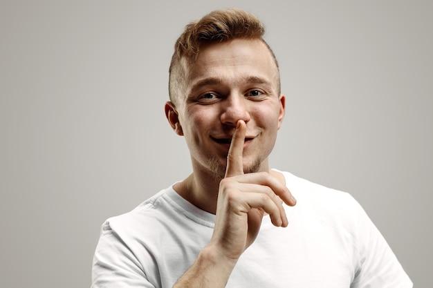 침묵을 지키십시오. 카메라를보고 회색 배경에 서있는 동안 입술에 손가락을 잡고 흰 셔츠에 잘 생긴 젊은 남자