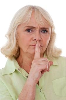 조용히 해! 흰색 배경에 격리된 채 카메라를 쳐다보며 입에 손가락을 대고 있는 진지한 시니어 여성