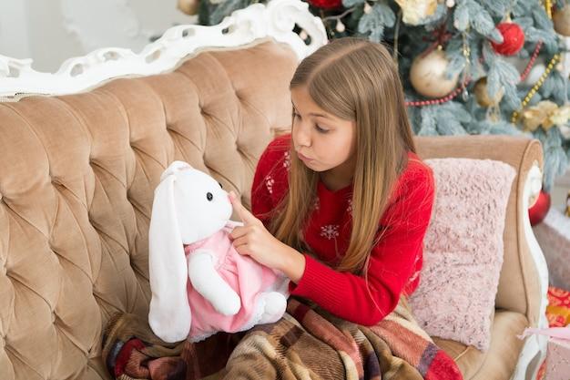 침묵을 지키십시오. 작은 소녀는 토끼 장난감의 입에 손가락을 잡고 있습니다. 어린 아이가 부드러운 장난감을 가지고 노는 것입니다. 크리스마스 트리에서 귀여운 토끼와 어린 소녀입니다. 새해 선물을 가진 작은 아이. 최고의 크리스마스 장난감.