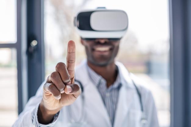 Соблюдай тишину. веселая брюнетка поднимает указательный палец во время тестирования маски для виртуального зрения