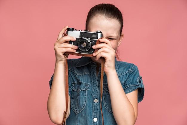 Продолжай улыбаться. маленькая девочка держит старинный фотоаппарат и снимает кого-то на нем. девушка довольна фотосессией. крытый студийный снимок, изолированные на розовом фоне
