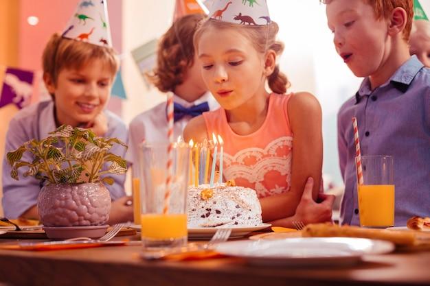 계속 웃으세요. 촛불을 불고있는 동안 테이블에 기대어 세심 한 소녀