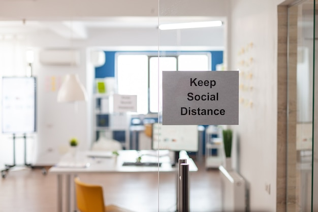 Covid 19コロナウイルスのパンデミックの間、空のオフィスのガラスの壁に社会的距離のサインを付けておきます。誰もいないビジネスワークプレイスインテリア、経済危機。