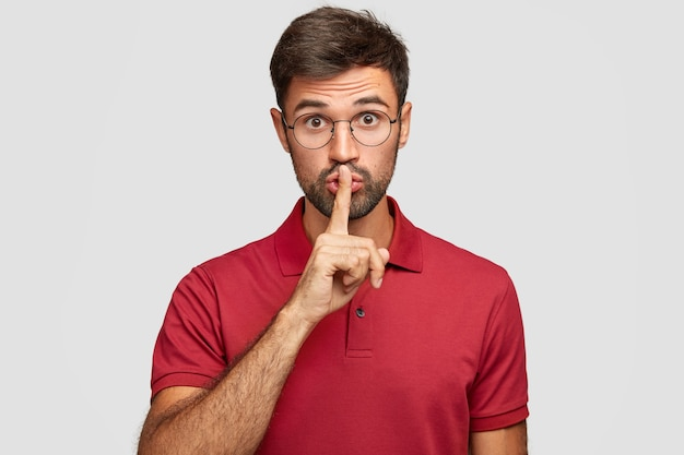 Keep voice down. attractive surprised bearded male makes shush gesture, demnads shut up, wears casual bright red t-shirt, poses against white wall. people, hush, conspiracy, secret concept