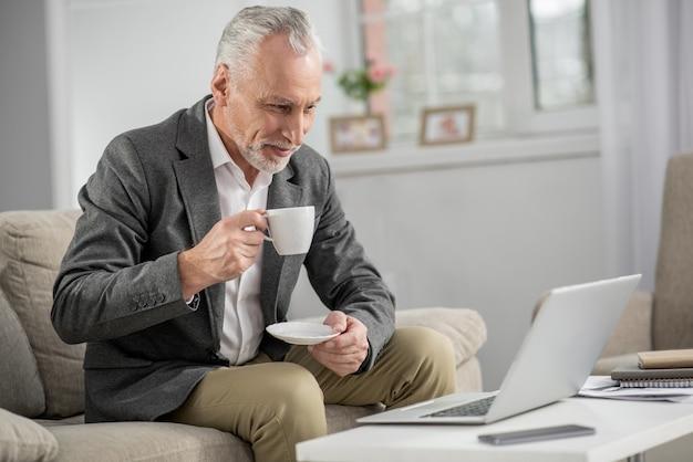 주의를 기울이십시오. 매력적인 사업가 오른손에 컵을 들고 컴퓨터를 보면서 그의 얼굴에 미소를 유지