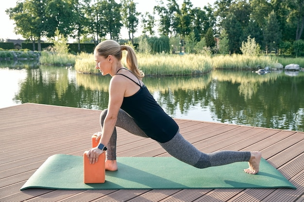 Keep your body healthy sporty attractive woman in sportswear using yoga blocks or bricks while