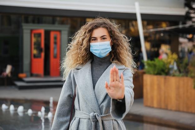 Сохраняйте социальную дистанцию. женщина в лицевой маске защиты от вирусов, показывая жест остановить инфекцию.