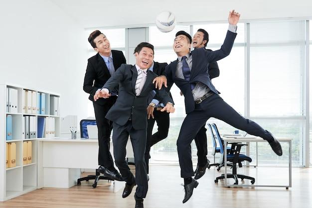 Радостные коллеги играют в keepie-uppie