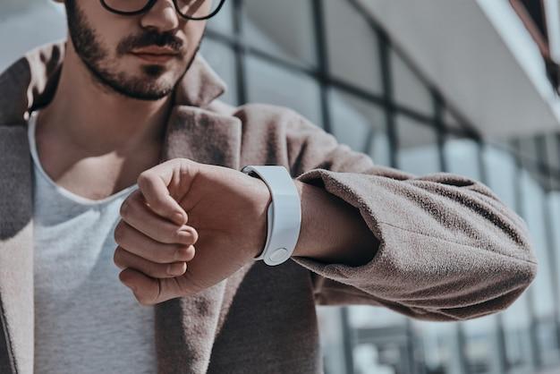 시간을 주시하십시오. 야외에서 서있는 동안 그의 시계를보고 안경에 젊은 현대인의 근접