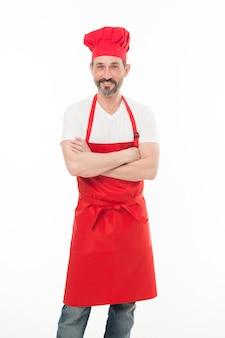 自信を持って腕を組んでください。シェフの帽子とエプロンでひげを生やした成熟した男。よだれかけのエプロンを身に着けているひげと口ひげを生やした上級料理人。赤い調理エプロンで成熟したチーフクック。家庭料理。