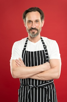 Keeping arms crossed with confidence. bearded mature man in striped apron. senior cook wear bib apron. mature person in cooking apron. aged master of the household. doing household. home cooking.