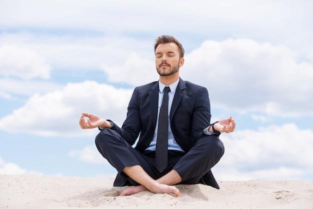 Сохраняя спокойствие в своей душе. красивый молодой бизнесмен медитирует, сидя в позе лотоса на песке и против голубого неба