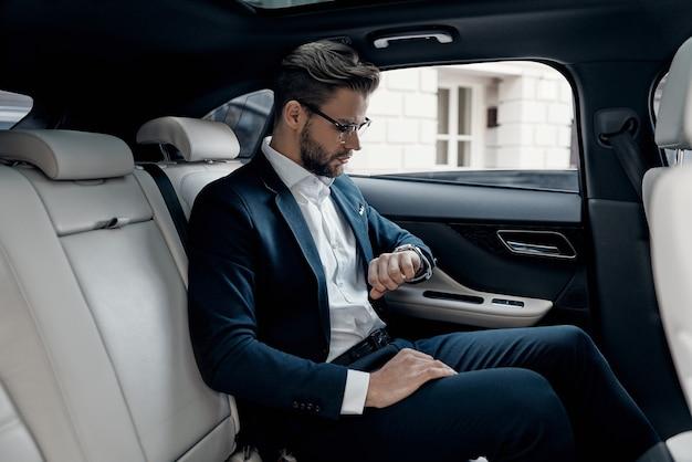 시간에 눈을 유지. 차에 앉아있는 동안 그의 시계를보고 전체 양복에 잘 생긴 젊은 남자
