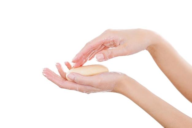그녀의 손을 깨끗하고 신선하게 유지합니다. 흰색에 고립 된 동안 비누로 손을 씻는 여자의 근접 프리미엄 사진