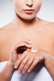 Держит руки молодыми и свежими. обрезанное изображение зрелой женщины, завернутой в полотенце, намазывающего крем, стоя на сером фоне