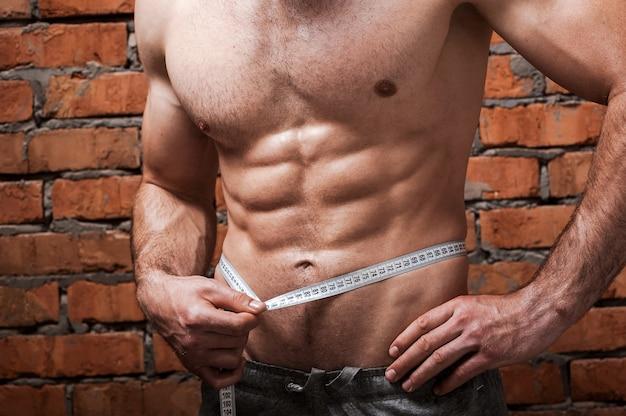 彼の体を健康に保つ。測定テープで彼の腰を測定する筋肉の男のクローズアップ