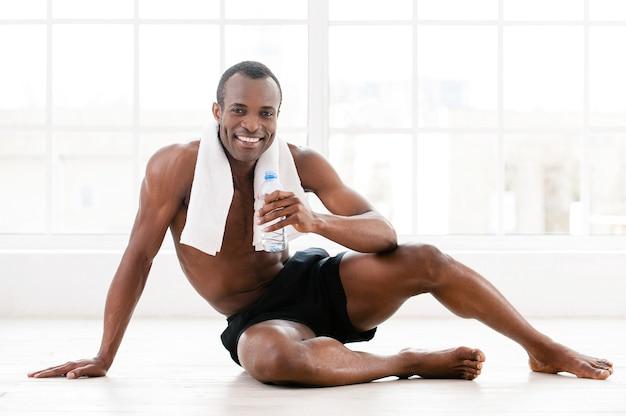 Поддерживает свое тело в форме. веселый молодой африканец сидит на полу и держит бутылку с водой