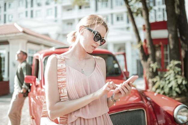 연락 유지. 남편 앞에 서 있는 아름다운 여성이 차에 기대어 가장 친한 친구와 문자를 주고받았습니다.
