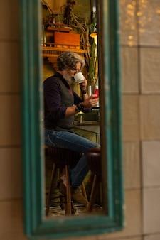 連絡を取りあっています。コーヒーを飲みながら喫茶店に座って妻にメッセージを書いている集中男性。