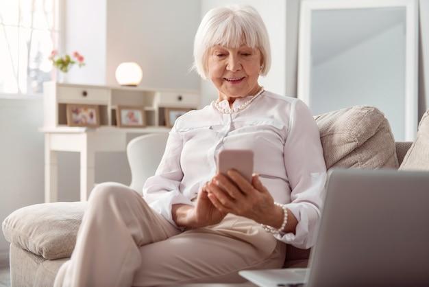 連絡を取りあっています。居間のソファに座って、笑顔で子供にテキストメッセージを送信する快適な年配の女性