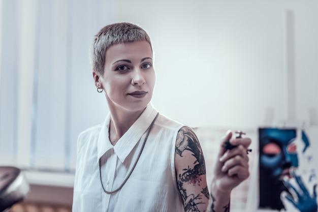 Хранение чернил в машине. улыбающаяся женщина со спокойным макияжем, несущая свою тату-машину во время насыщенного рабочего дня