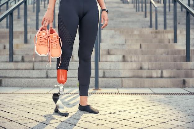 Сохраняю свое тело здоровым. обрезанное фото женщины с протезом ноги в спортивной одежде.