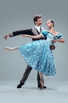 한 방향 유지. 회색 스튜디오 배경에 고립 된 아름 다운 현대 볼룸 댄서. 왈츠, 탱고, 슬로우 폭스, 퀵 스텝을 춤추는 감각적 인 프로페셔널 아티스트. 유연하고 무중력.