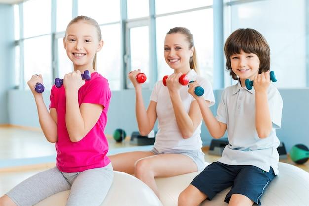 私たちの体を健康に保つ。陽気な母親と2人の子供が一緒にフィットネスボールに座ってヘルスクラブでダンベルで運動