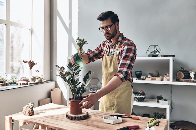 植物を水分補給する。鉢植えの植物に水をまくエプロンのハンサムな若い男