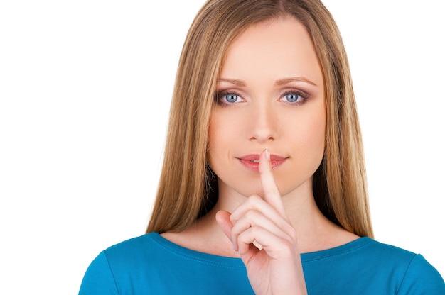 Молчание. привлекательная молодая женщина смотрит в камеру и держит палец на губах, стоя изолированной на белом