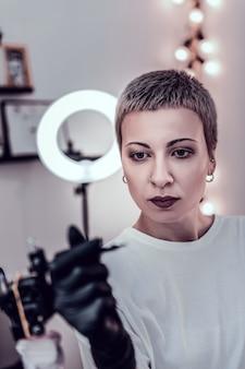 特別な設備を保つ。彼女のマシンの詳細を観察している短い髪と大きな目を持つ女性のマスター