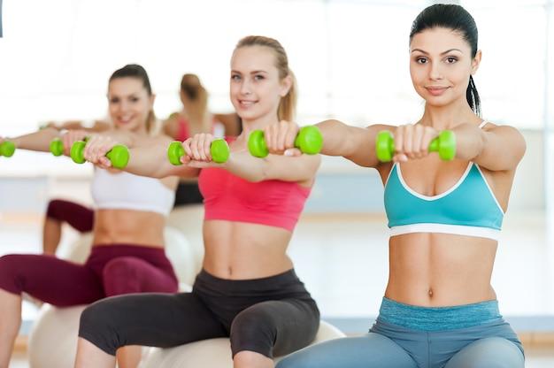 彼らの体を形に保つ。スポーツウェアの3人の美しい若い女性