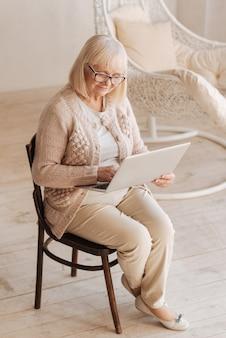 Идти в ногу со временем. позитивная приятная старшая женщина, держащая ноутбук и работающая над ним, сидя на стуле