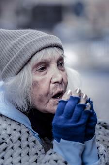 暖かく保つ。暖かくしようとしている間彼女の手で呼吸して落ち込んでいる高齢女性