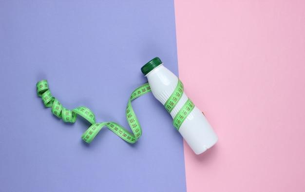 Kefir bottle, measuring tape on a pastel paper