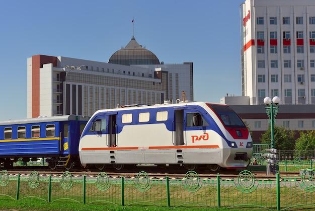 ケメロヴォ、シベリア、ロシア-09.01.2021:青い空の下で市内中心部のpionerskaya駅にある小さな機関車