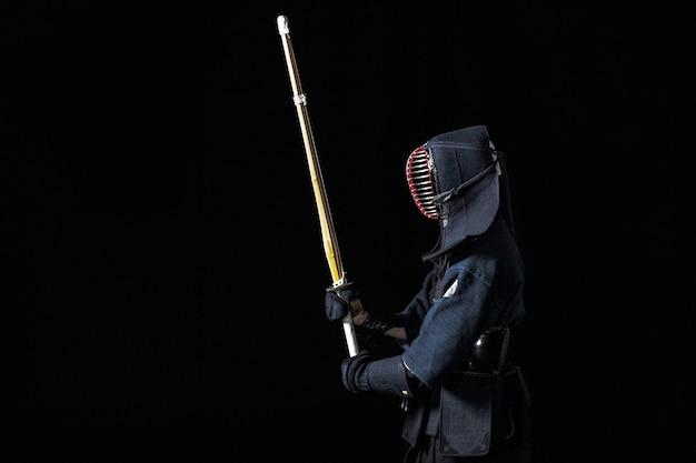 黒の背景に竹刀を持った剣道ファイター