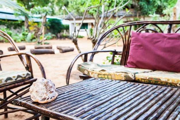 Кения. элегантная мебель из дерева в африканском саду
