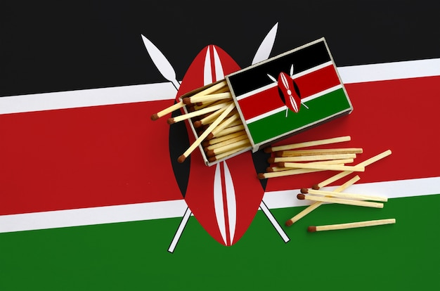 Kenya flag  is shown on an open matchbox, from which several matches fall and lies on a large flag