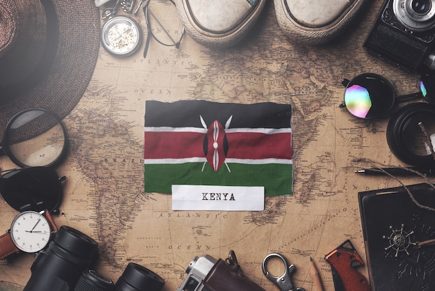 Kenya flag between traveler's accessories on old vintage map. overhead shot