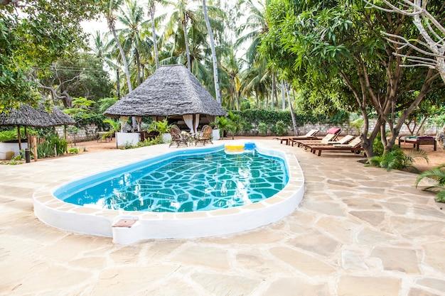 ケニア。背景に木で作られた典型的な地元の椅子とアフリカの庭の豪華なスイミングプール