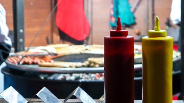 선택적 포커스가 있는 전경 클로즈업에서 거리 그릴 근처의 플라스틱 튜브에 케첩과 마요네즈. 바베큐, 길거리 음식 축제. 고기 소스 두 캔. 빨간색과 노란색 컨테이너입니다.