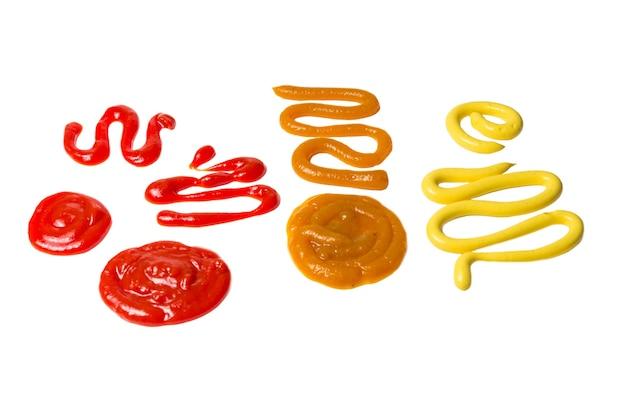 Кетчуп и брызги желтого соуса, изолированные на белом фоне.