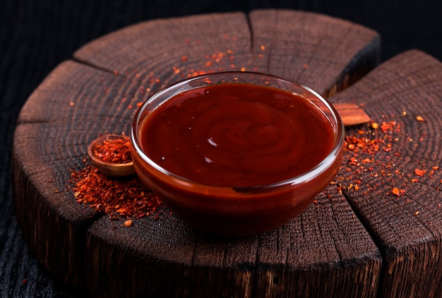 Ketchup in bowl on dark wooden background