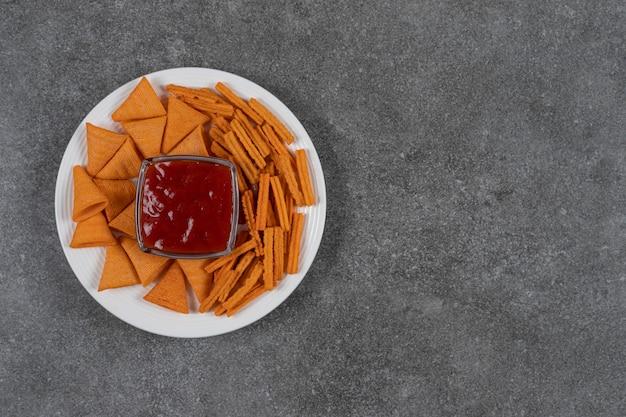 Ketchup, patatine di mais e pane secco sul piatto sulla superficie in marmo