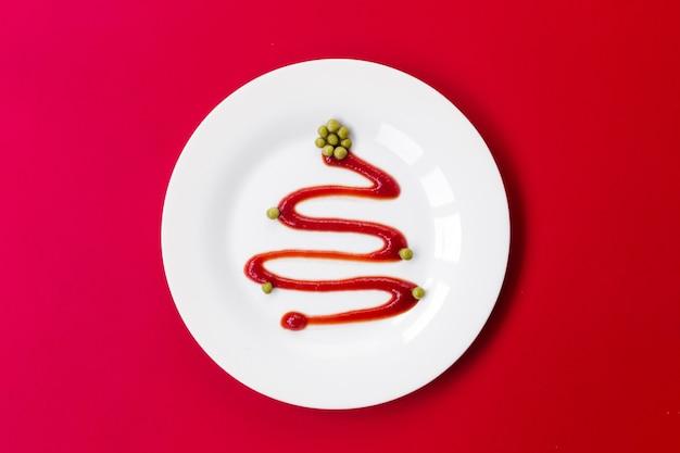 Кетчуп в белой тарелке похож на елку