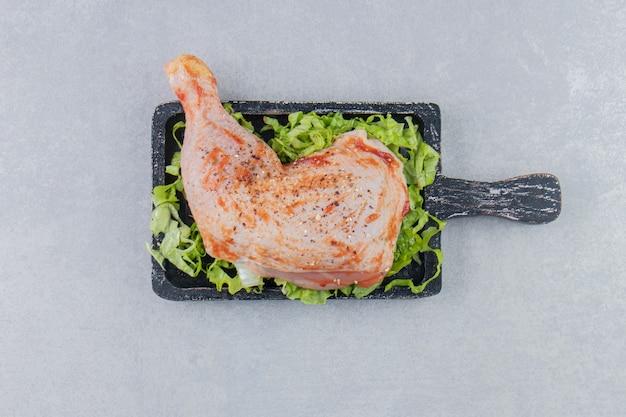 Кетчуп мясо и зелень на доске, на белой поверхности